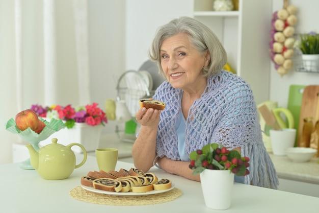 Porträt einer glücklichen älteren frau mit leckerem kuchen zu hause
