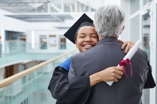 Porträt einer glücklichen afroamerikanischen frau, die ein abschlusskleid trägt, das den vater oder den college-professor drinnen umarmt, kopierraum