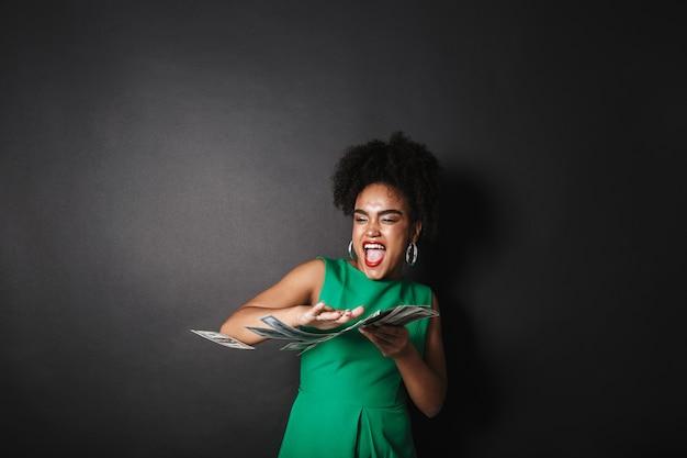 Porträt einer glücklichen afroamerikanischen frau, die kleid trägt, das über schwarzer wand steht