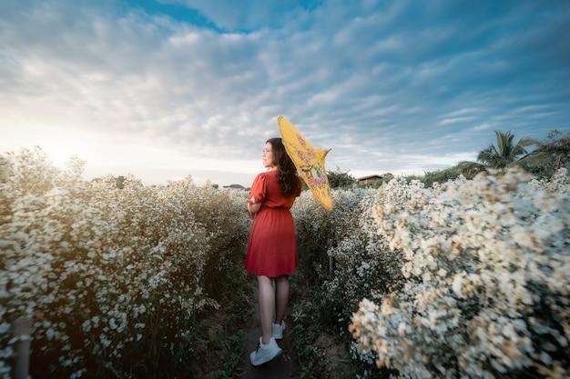 Porträt einer glücklichen asiatischen frau mit rotem kleid, die einen gelben regenschirm genießt, der im weißen blühenden oder weißen margarita-flowe-feld im garten von chiang mai, thailand, urlaub genießt