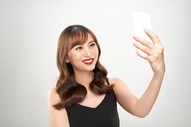 Porträt einer glücklichen asiatischen geschäftsfrau unter verwendung des mobiltelefons lokalisiert über weißem hintergrund