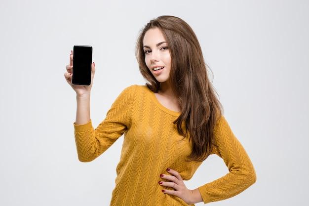 Porträt einer glücklichen, beiläufigen frau, die einen leeren smartphone-bildschirm zeigt, der auf einem weißen hintergrund isoliert ist