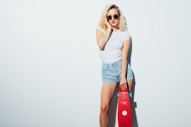 Porträt einer glücklichen blonden frau in der sonnenbrille, die mit skateboard beim stehen und lachen lokalisiert über weißer wand aufwirft