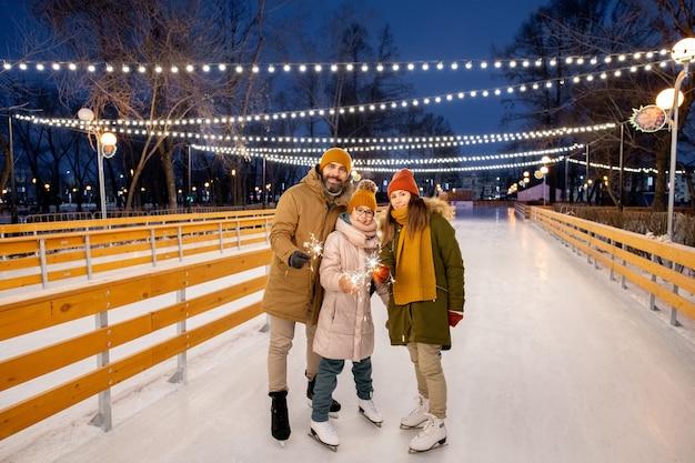 Porträt einer glücklichen dreiköpfigen familie mit wunderkerzen, die während der weihnachtsferien auf der eisbahn im freien stehen