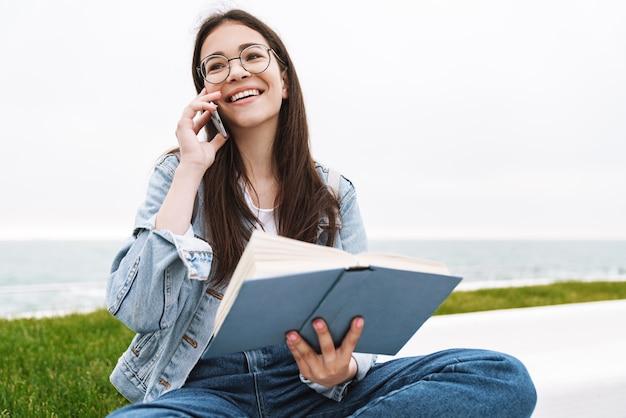 Porträt einer glücklichen emotionalen jungen hübschen studentin, die eine brille trägt und im freien ein buch liest, das mit dem handy spricht.