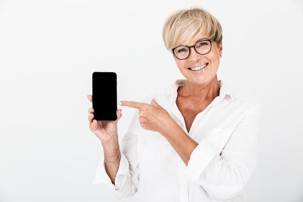 Porträt einer glücklichen erwachsenen frau mit kurzen blonden haaren, die ein handy hält und einen schwarzen bildschirm zeigt, der über einer weißen wand im studio isoliert ist?