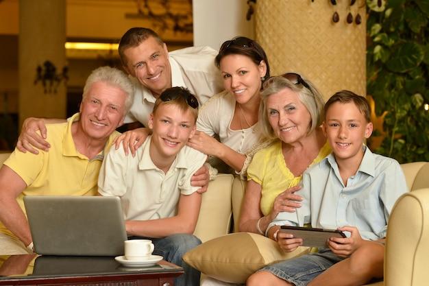 Porträt einer glücklichen familie, die mit laptop sitzt