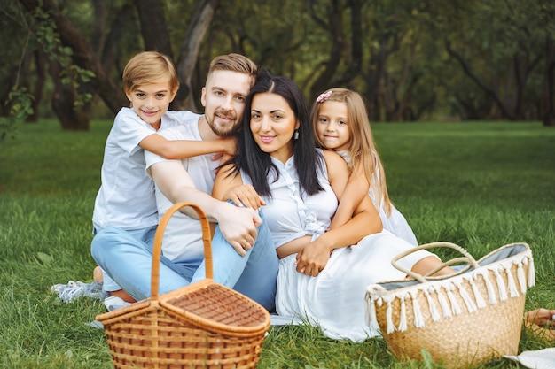 Porträt einer glücklichen familie, die umarmt und in die kamera schaut, während auf dem rasen während eines picknicks in einem grünen garten entspannt wird
