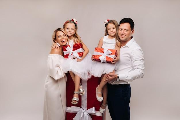 Porträt einer glücklichen familie mit geschenken in den händen auf beigem hintergrund.