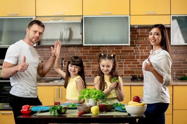 Porträt einer glücklichen familie, mutter, vater und zwei töchter, die salate in der küche zu hause kochen