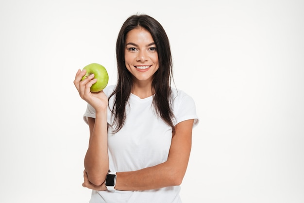 Porträt einer glücklichen fit frau, die grünen apfel hält