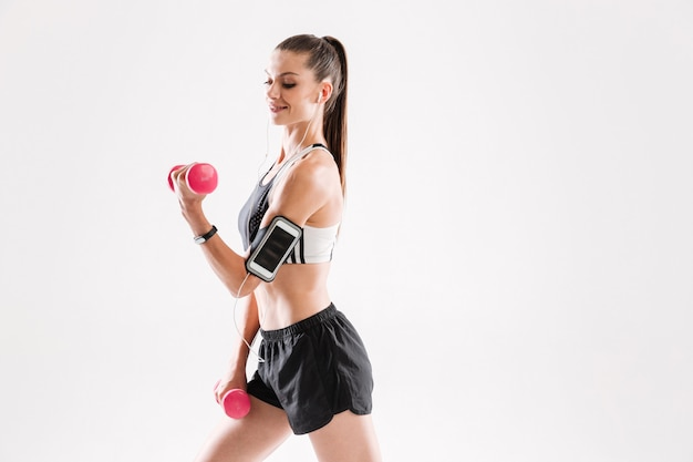Porträt einer glücklichen fitnessfrau in der sportbekleidung, die musik hört