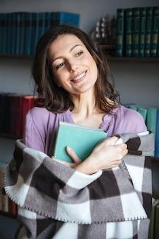 Porträt einer glücklichen frau bedeckt in der decke, die buch hält