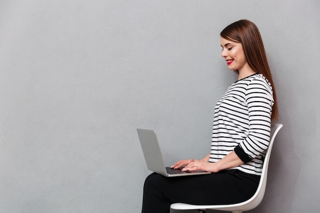 Porträt einer glücklichen frau, die auf stuhl sitzt