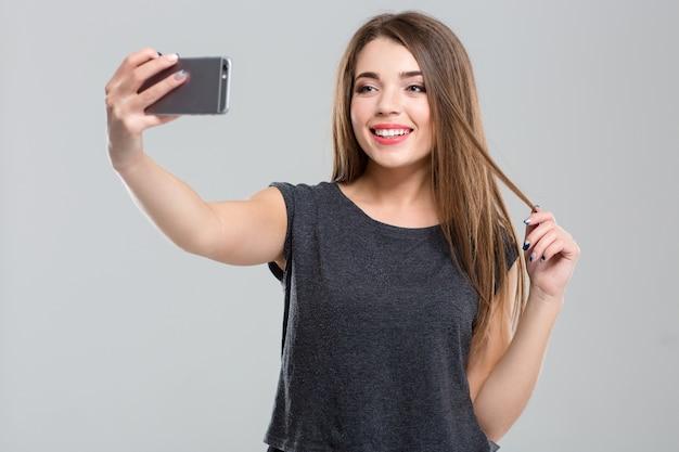Porträt einer glücklichen frau, die ein selfie-foto auf dem smartphone macht, isoliert auf weißem hintergrund