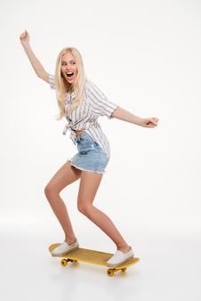Porträt einer glücklichen frau, die ein skateboard reitet