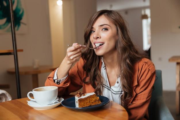 Porträt einer glücklichen frau, die ein stück kuchen isst