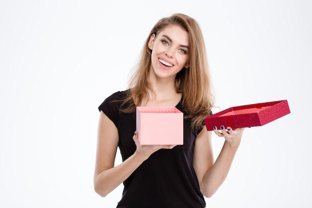 Porträt einer glücklichen frau, die geschenkbox auf einem weißen hintergrund öffnet