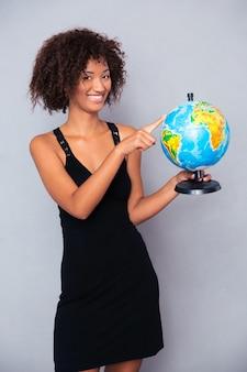 Porträt einer glücklichen frau, die globus über graue wand hält