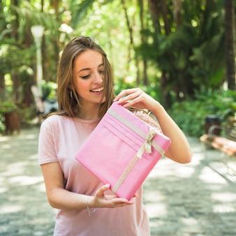 Porträt einer glücklichen frau, die rosa geschenkbox auspackt