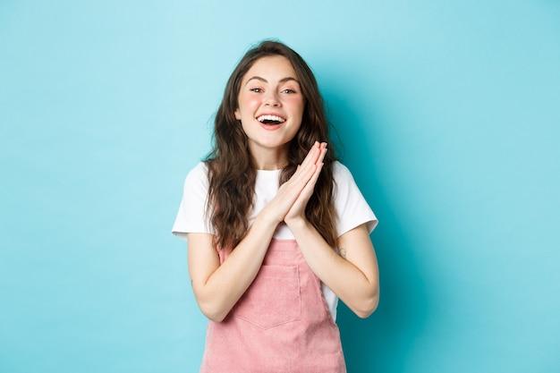 Porträt einer glücklichen frau, die sich über gute nachrichten freut, hände von dealight klatscht und lächelt, sich für geschenk bedankt, zufrieden aussieht und vor blauem hintergrund steht.
