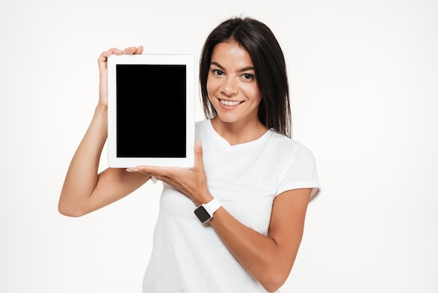 Porträt einer glücklichen frau, die tablet-computer mit leerem bildschirm präsentiert