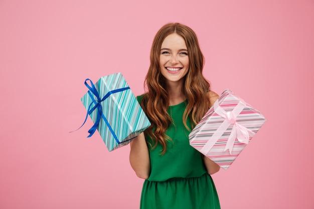 Porträt einer glücklichen frau im kleid, das geschenkboxen hält