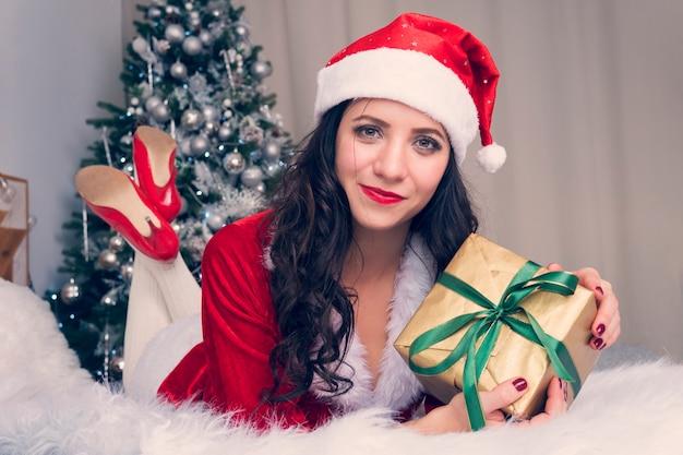 Porträt einer glücklichen frau im weihnachtsmann-tuch, die viele geschenkboxen auf dem für weihnachtswohnung dekorierten hintergrund umarmt. mädchen mit weihnachtsgeschenk auf dem bett ist glücklich und ulybaetsya.