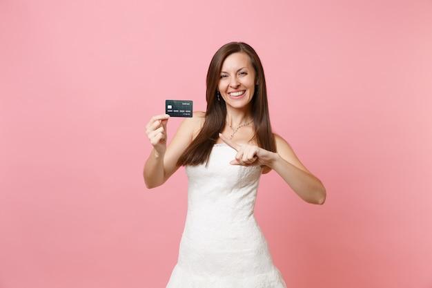 Porträt einer glücklichen frau im weißen kleid, die mit dem zeigefinger auf die kreditkarte zeigt