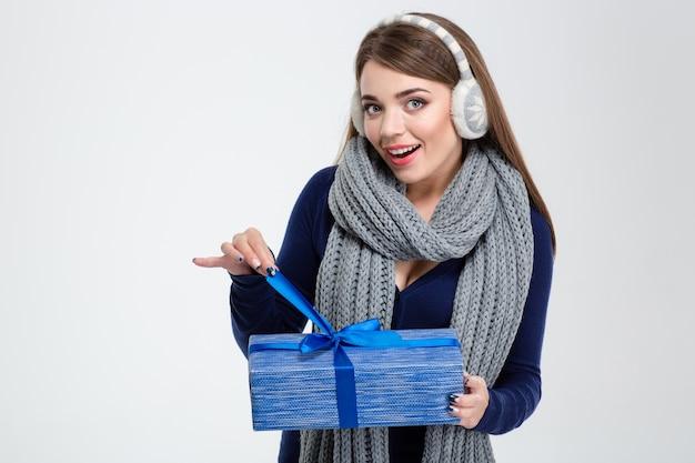 Porträt einer glücklichen frau im wintertuch, die geschenkbox lokalisiert auf einem weißen hintergrund hält