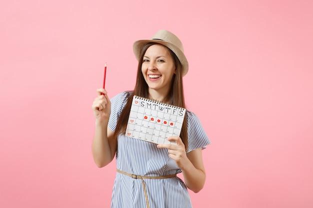 Porträt einer glücklichen frau in blauem kleid, hut mit rotem bleistift, kalender für weibliche perioden zur überprüfung der menstruationstage einzeln auf rosafarbenem hintergrund. medizinisches gesundheitswesen, gynäkologisches konzept. platz kopieren