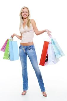 Porträt einer glücklichen frau in voller länge nach dem einkaufen mit einkäufen
