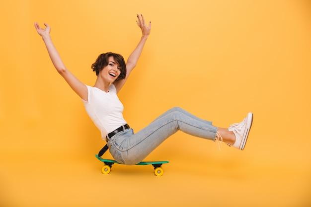 Porträt einer glücklichen fröhlichen frau, die auf einem skateboard sitzt
