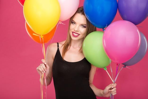 Porträt einer glücklichen, fröhlichen, schönen, attraktiven jungen frau mit bunten luftballons Premium Fotos
