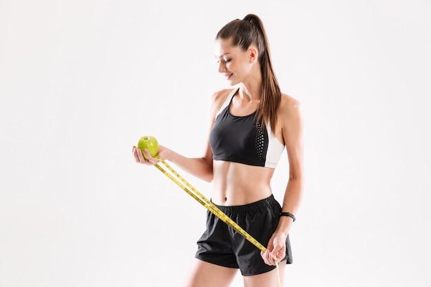 Porträt einer glücklichen gesunden fitnessfrau, die grünen apfel hält