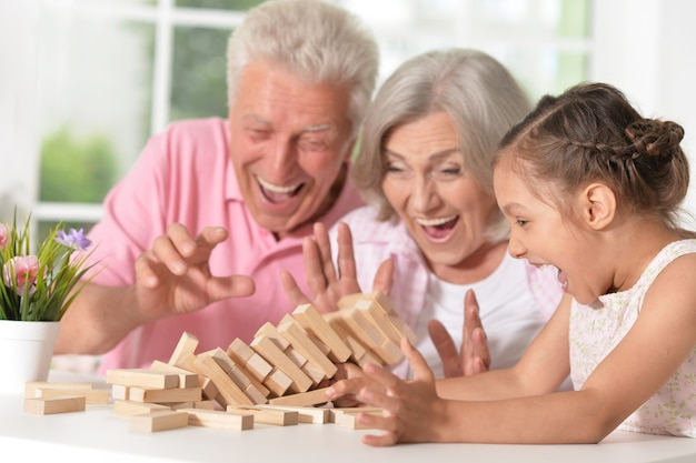 Porträt einer glücklichen großeltern mit enkelin, die zusammen spielt