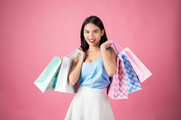 Porträt einer glücklichen hübschen frau, die einkaufstaschen hält