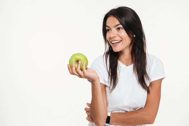 Porträt einer glücklichen hübschen frau, die grünen apfel hält