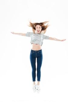 Porträt einer glücklichen hübschen jungen frau, die mit erhobenen händen springt