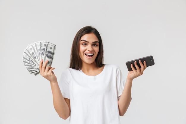 Porträt einer glücklichen hübschen jungen frau lässig gekleidet isoliert auf weiß, geldbanknoten zeigend, unter verwendung des mobiltelefons