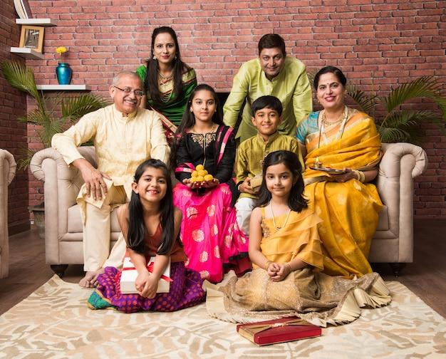 Porträt einer glücklichen indischen familie in traditioneller kleidung, die auf einem sofa im innenbereich sitzt