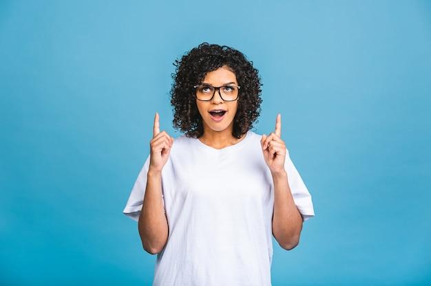 Porträt einer glücklichen jungen afroamerikanerfrau, die finger weg auf kopienraum lokalisiert über blauem hintergrund zeigt.