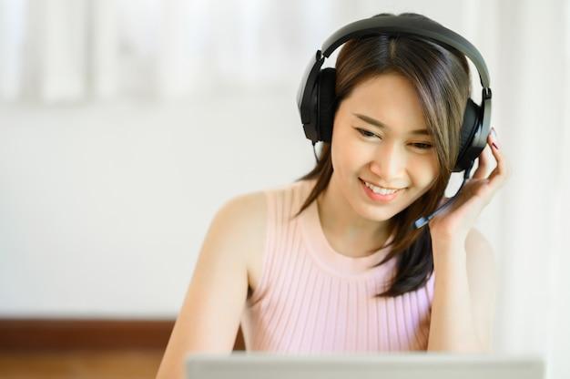 Porträt einer glücklichen jungen asiatin, die ein headset trägt, während sie zu hause an einem notebook arbeitet working
