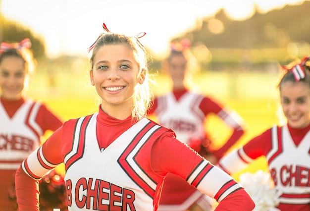 Porträt einer glücklichen jungen cheerleaderin in aktion im freien
