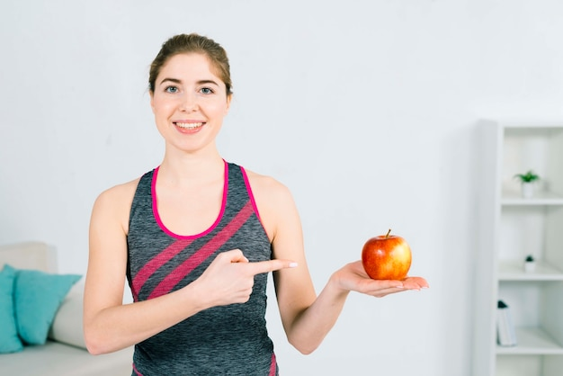 Porträt einer glücklichen jungen eignungsfrau, die in der hand roten apfel zeigt