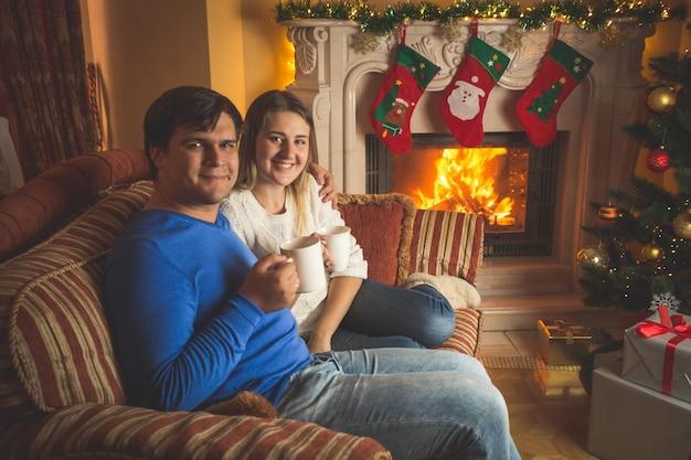 Porträt einer glücklichen jungen familie, die tee auf dem sofa am kamin trinkt