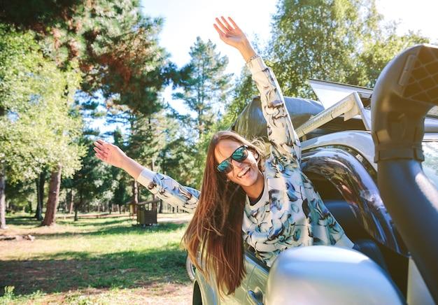 Porträt einer glücklichen jungen frau, die an einem sonnigen tag ihre arme durch das fensterauto hebt