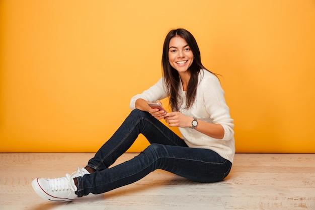 Porträt einer glücklichen jungen frau, die auf einem boden sitzt