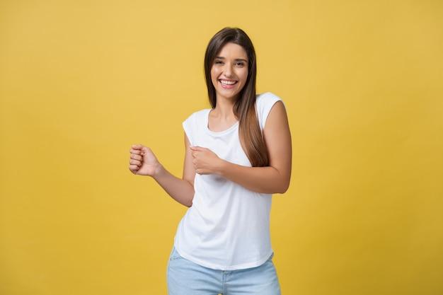 Porträt einer glücklichen jungen frau, die auf gelbem hintergrund tanzt