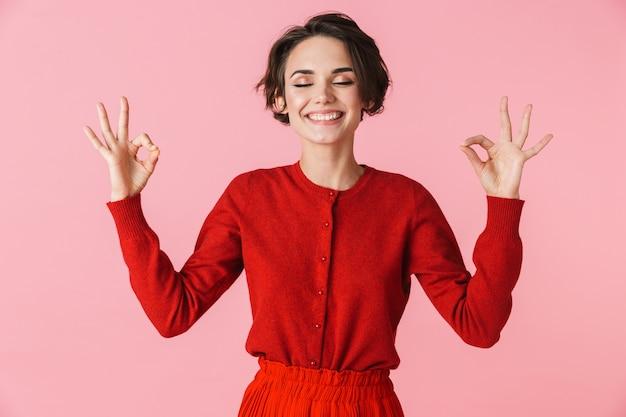 Porträt einer glücklichen jungen frau, die rote kleidung trägt, die isoliert steht, ok
